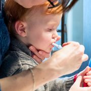 Cute Redhead Toddler Boy Having his Teeth Brushed by his Mother